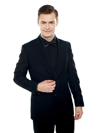 undoing: Smiling young man in party wear attire. Undoing coat button Stock Photo