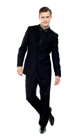 Isolated young man standing with crossed legs dressed in party wear photo