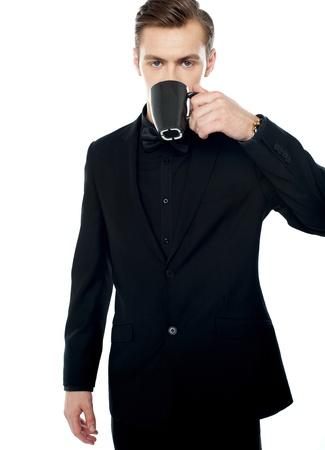 hombre tomando cafe: Inteligente joven que el consumo de café en la taza de negro sobre fondo blanco