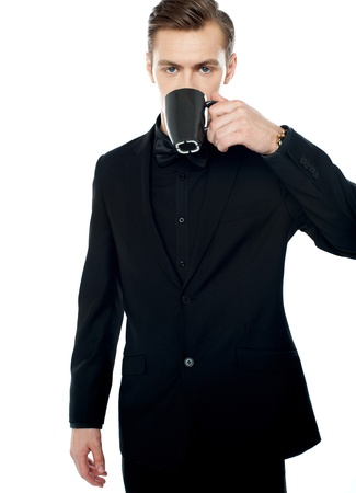 sipping: Smart young man drinking coffee in black cup over white background