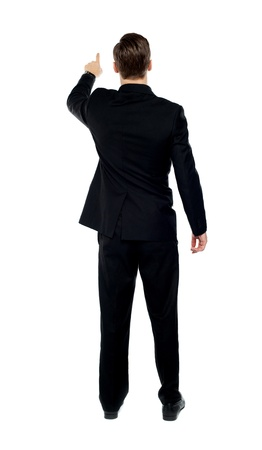 Rear view of a male model pointing at copy space over white background photo