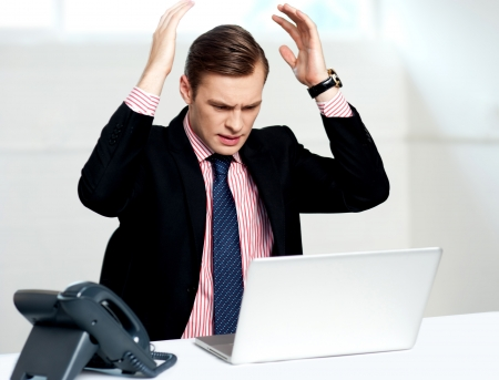 Disappointed businessman looking at laptop with hands above his head photo