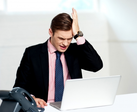 Unhappy businessperson looking at his laptop. Business loss photo