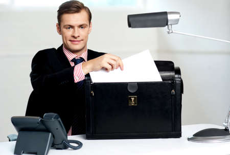 Male executive keeping documents safely in his briefcase photo