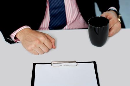Closeup of businessman holding empty cup. Office desk. Closeup shot photo