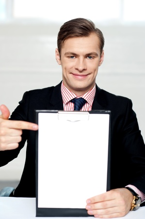 Smiling man pointing towards blank clipboard. Indoor shot photo