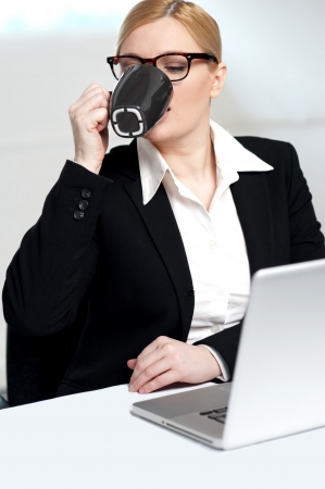Corporate lady drinking coffee at work photo