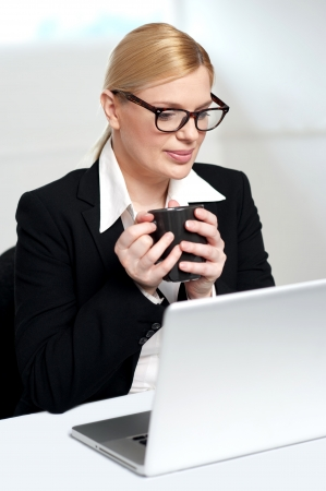 Female executive looking at laptop and holding coffee mug in hands photo