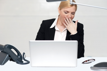 tried: Tried woman sitting with hand on her mouth in front of laptop. It has been a long day at work Stock Photo