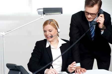 Male executive attending clients call while female secretary enjoys the conversation photo