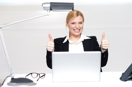 Cheerful businesswoman in office with laptop gesturing double thumbs up photo