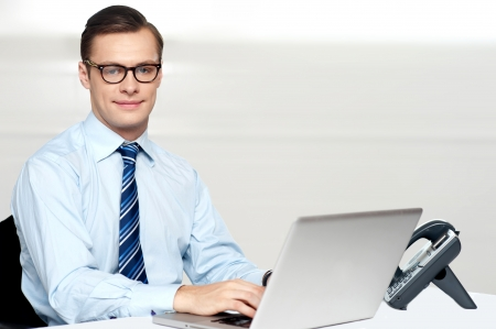 Handsome corporate male tying on laptop. working in office Stock Photo - 14396839