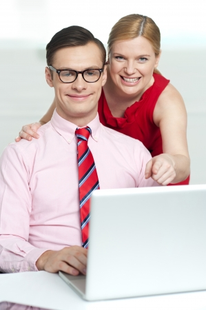 Corporate couple enjoying videos on laptop while woman pointing at laptop Stock Photo - 14396870