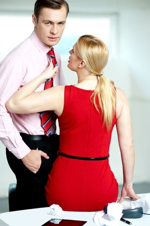 Female secretary feeling naughty. Holding mans tie and looking into his eyes photo