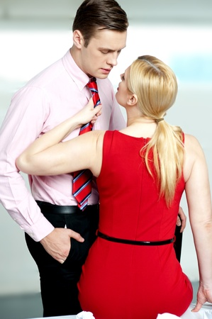 Woman pulling man from his tie. Feeling naughty. About to kiss inside office