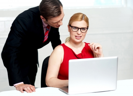 Young business team working in office. Woman operating laptop while man standing behind her photo