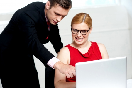 Business team in action. Man pointing at laptop while woman looks into it photo