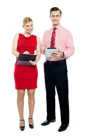 Full length portraits of business people. Man holding tablet pc and woman writing on clipboard photo