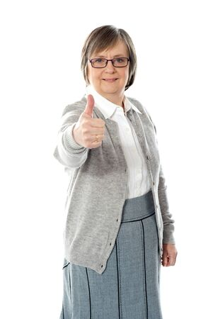 Old lady showing thumbs up gesture isolated against white background photo