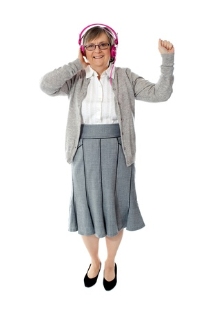 Old woman enjoying music through pink headphones aginst white background photo