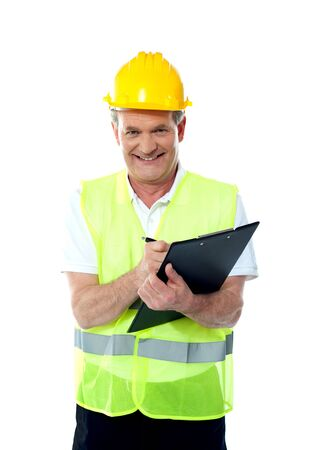 Smiling senior construction engineer writing on documents wearing safty hat and jacket photo