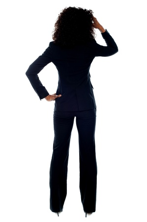 scratching head: Rear view portrait of confused businesswoman looking at white wall