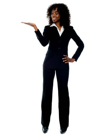 Full length portrait of corporate african lady presenting copy space against white background photo