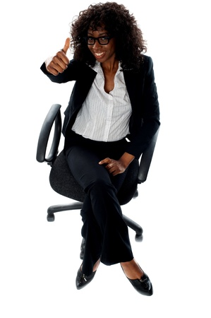 Seated woman with thumbs up gesture isolated over white background photo