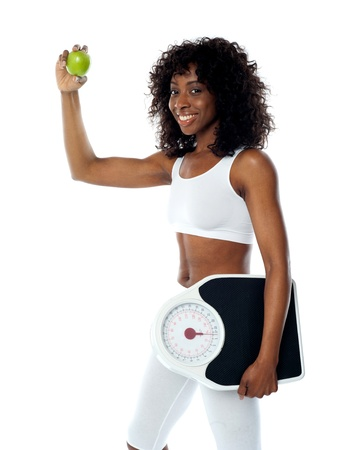 Athlete holding green apple and weighing machine wearing white sport outfit photo