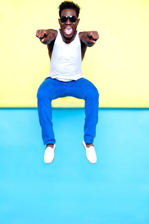 Excited african male jumping and pointing at you  Extremely happy and wearing sunglasses photo