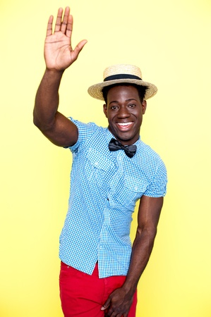 Casual young african guy posing with raised arm  Wearing hat and cool attire photo