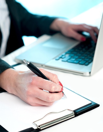 Closeup of woman copying data from laptop to notepad, Making important notes photo