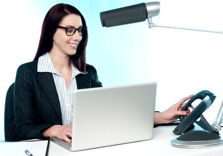 answering phone: Respondiendo Mujer secretaria llamada de tel�fono en la oficina. Trabajo en la computadora port�til