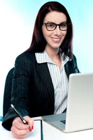 Corporate lady posing with pen in hand working on some business document photo