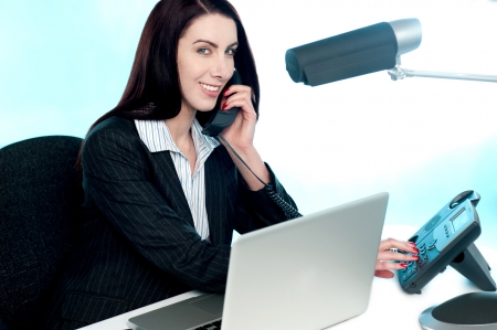 answering phone: Secretary at work in office talking to client via phone call. Smiling and looking at camera