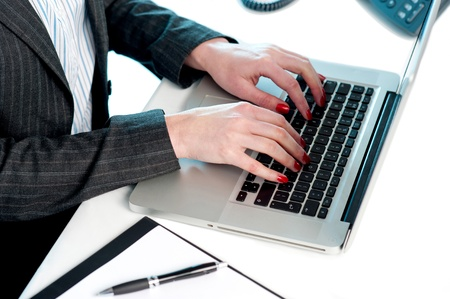 Females hands typing on laptop keypad. Cropped image. Busy office desk photo