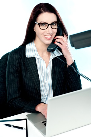 simultaneously: Female executive speaking on phone and simultaneously working on laptop Stock Photo
