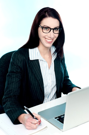 Smiling young woman at desk copying  notes from laptop to notepad photo