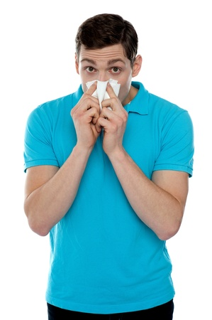 Young guy suffering from cold. Holding handkerchief and sneezing photo