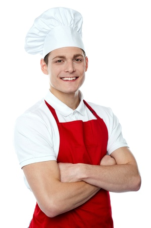 Smiling young chef posing with crossed arms against white background photo