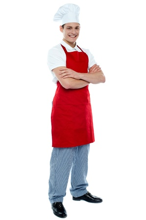 Full length shot of handsome smiling male chef posing with crossed arms photo