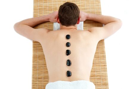 Man receiving hot stone therapy massage. Rear view portrait photo