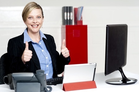 Senior businesswoman gesturing thumbs up working actively in office Stock Photo - 14552947
