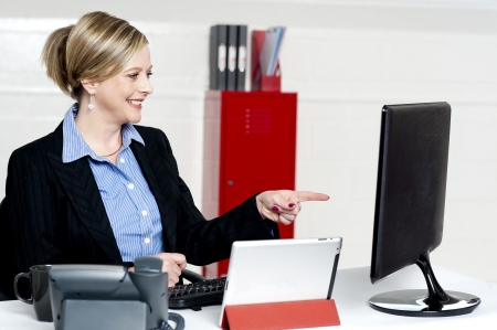 Female executive pointing at computer screen sitting on desk and working photo