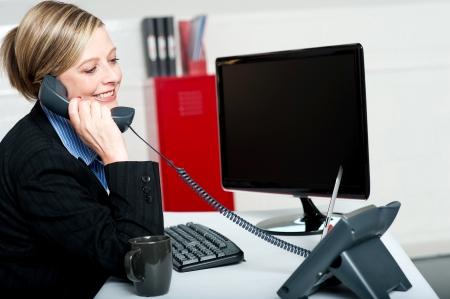 llamando: Secretaria de sexo femenino responder jefes llaman e informar a las actualizaciones Foto de archivo
