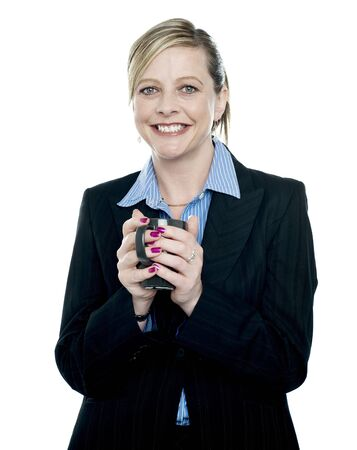 Cheerful female secretary holding coffee cup in front of camera photo