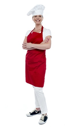 Full length portrait of pretty female cook standing with arms crossed over white photo