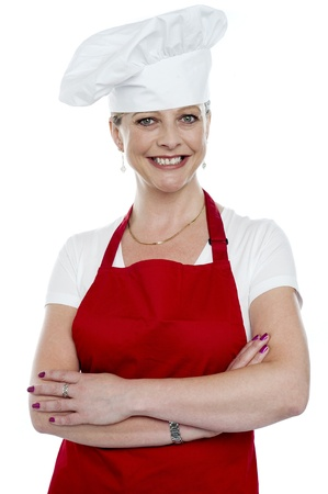 Smiling female cook with crossed arms posing in front of camera photo