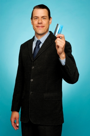 Male executive showing credit card to camera against gradient background photo