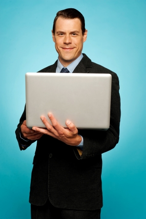 Attractive smiling businessman holding laptop and surfing web photo